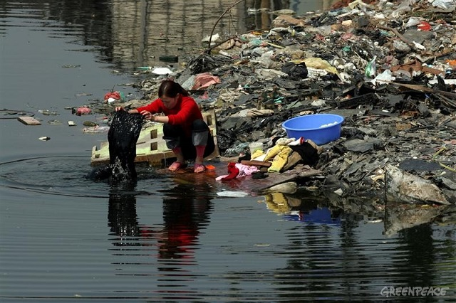 ewaste_greenpeace_guiyu-woman-river.jpg